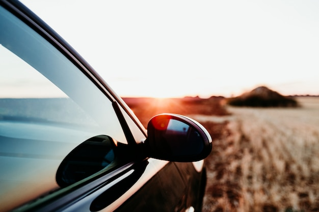 Close up view of a car and rear mirror at sunset on a field. travel concept