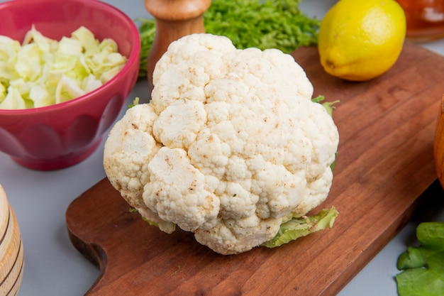 Close-up view of cauliflower and lemon on cutting board with sliced cabbage in bowl bunch of coriander on blue background
