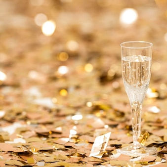 Close-up view of champagne glass with confetti