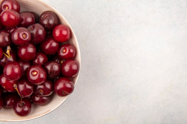 Close-up view of cherries in bowl and on white background with copy space