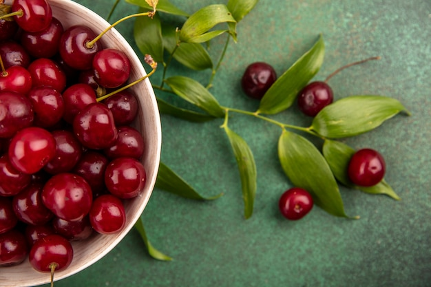 Close-up view of cherries in bowl with leaves and cherries on green background