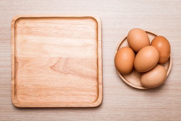 Close-up view of chicken eggs on wooden table background