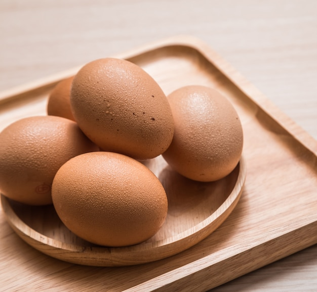Close up view of chicken eggs on wooden table