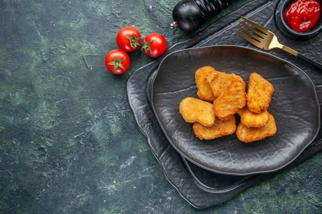 Vista ravvicinata delle pepite di pollo su un piatto nero e un'elegante forchetta ketchup su vassoio di colore scuro pomodori a fiore bianco sul lato sinistro