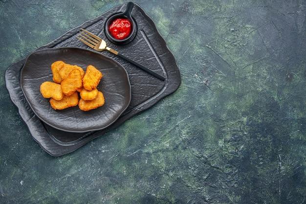 Vista ravvicinata delle pepite di pollo su un piatto nero e ketchup a forchetta sul lato destro su vassoio di colore scuro