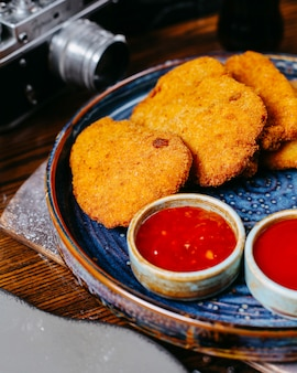 Close up view of chicken nuggets served with sweet chili sauce ketchup and mayonnaise on platter on dark