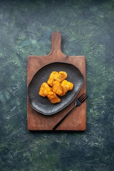 Close up view of chicken nuggets on wooden cutting board on dark surface with free space