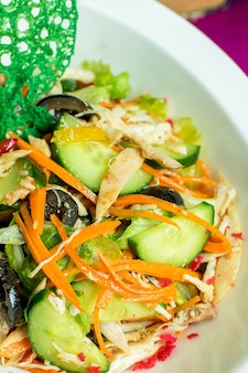 Close up view of chicken salad with chopped fresh vegetables and black olives in a bowl