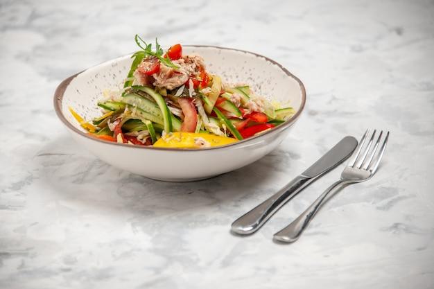 Vista ravvicinata dell'insalata di pollo con verdure e posate su una superficie bianca macchiata