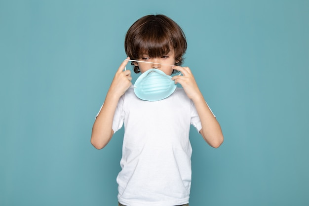 Close up, view child boy sweet in white t-shirt wearing blue respiratory protective sterile mask in white t-shirt on blue backgrond