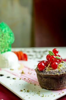 Close up view of chocolate muffin with red fresh currant