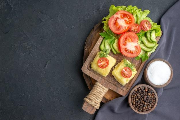 Vista ravvicinata di verdure fresche tritate formaggio su tagliere e spezie su asciugamano di colore scuro su superficie nera