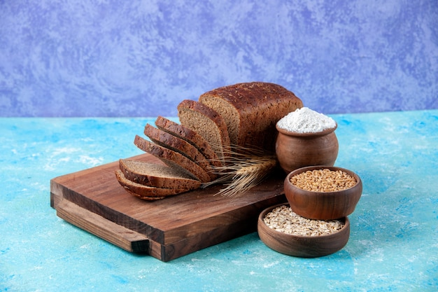 Vista ravvicinata di fette di pane nero tritate a metà su tavole di legno farina d'avena di grano in ciotole su sfondo blu ghiaccio chiaro