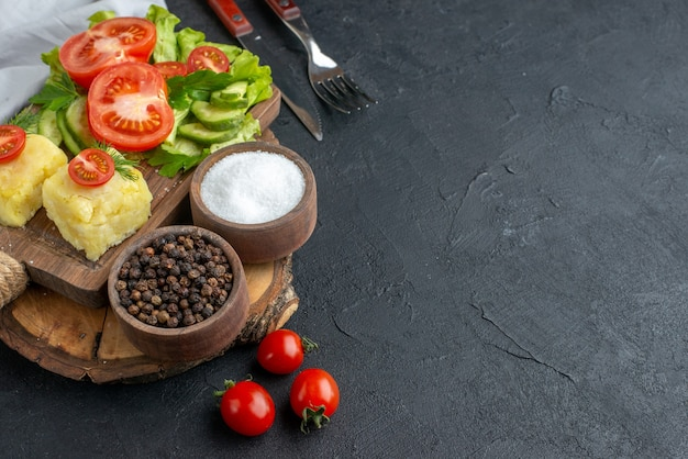 Close up view of chopped and whole fresh vegetables cheese on cutting board and spices cutlery set on black surface