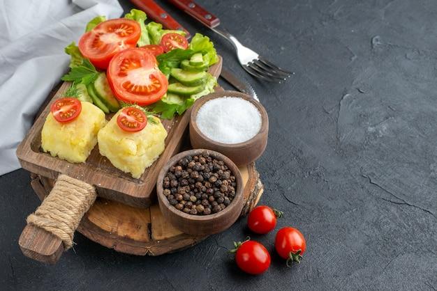 Vista ravvicinata di verdure fresche tritate e intere formaggio su tagliere e posate per spezie su superficie nera