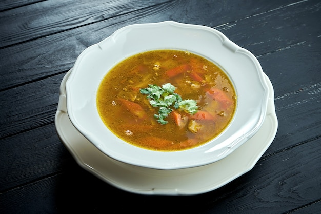 クローズアップビューチョルバスープまたは木製の表面に白いボウルに牛肉、ハーブ、唐辛子とシチュー、伝統的なトルコ料理