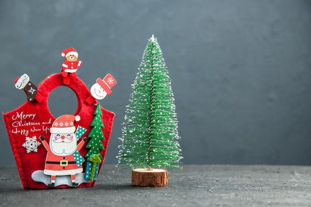 Vista ravvicinata dell'atmosfera natalizia con accessori decorativi sulla confezione regalo di capodanno e albero di natale sul lato destro su superficie scura