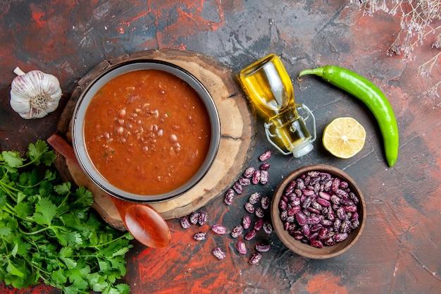Vista ravvicinata della classica zuppa di pomodoro in una ciotola blu cucchiaio sul vassoio in legno bottiglia di olio aglio sale e limone un mazzetto di verde su colori misti tabella