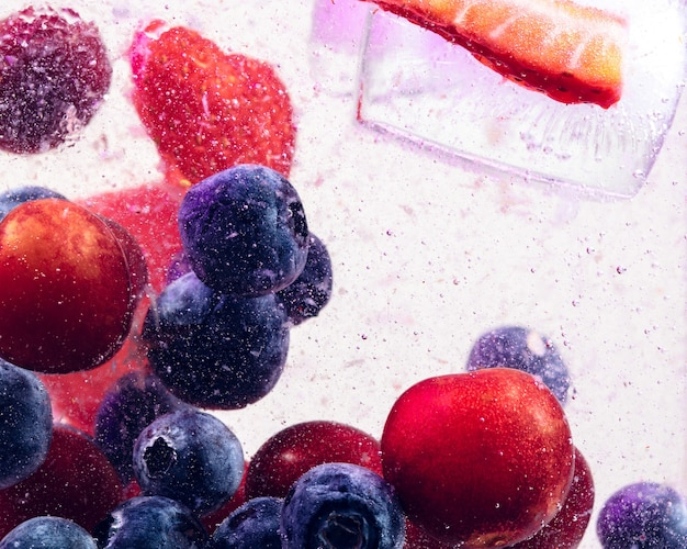 Close up view of the cold and fresh lemonade with bright berries and ice cubes in neon light.