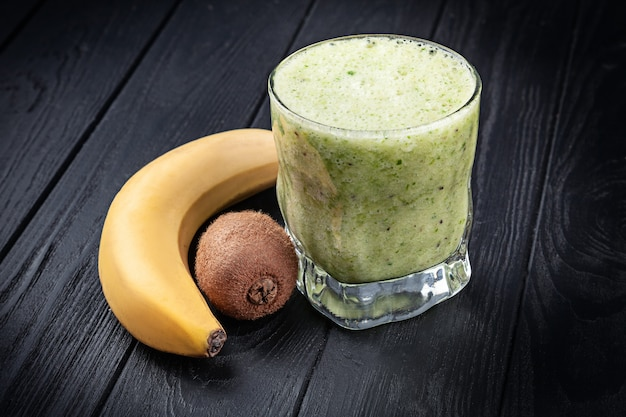 Close up view on cold glass with smoothie with spinach, banana and kiwi