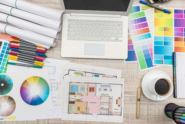 Close up view of color palette swatch and house building plans on office desk with laptop and cup of coffee for break.