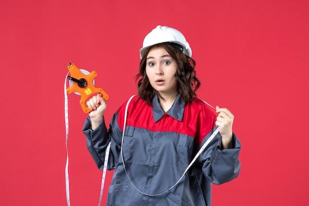 Vista ravvicinata dell'architetto femminile concentrato in uniforme che indossa elmetto con nastro di misurazione sulla parete rossa