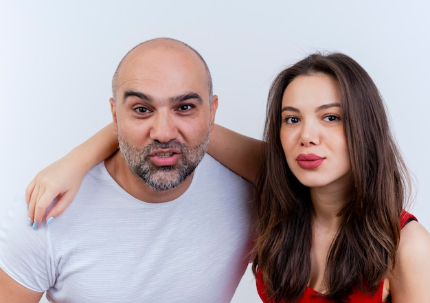 Close-up view of confident adult couple woman putting hand on man's shoulder both looking