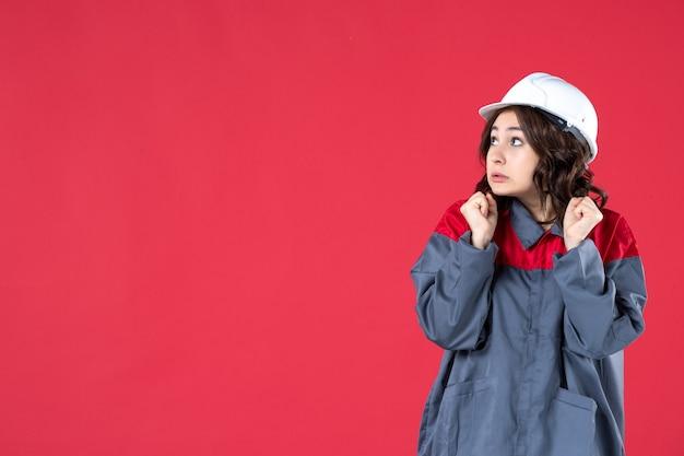 Vista ravvicinata del costruttore femminile confuso in uniforme con elmetto sulla parete rossa isolata
