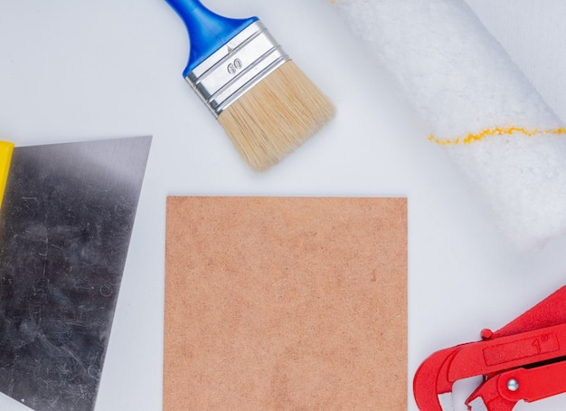 Close-up view of construction tools as paint brush and roller pipe wrench putty knife around mettlach tile on white background