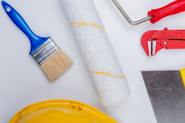 Close-up view of construction tools as paint brush and roller safety helmet pipe wrench and putty knife on white background