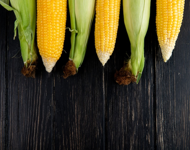 Close-up view of cooked and uncooked corns on black background with copy space