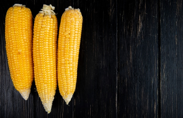 Close-up view of cooked whole corns on black background with copy space