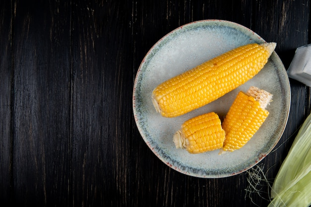 Close-up view of cooked whole and cut corns on right side and black background with copy space