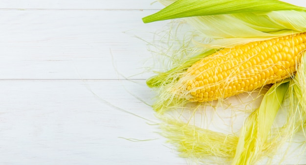 Close-up view of corn cob on right side and wooden background with copy space