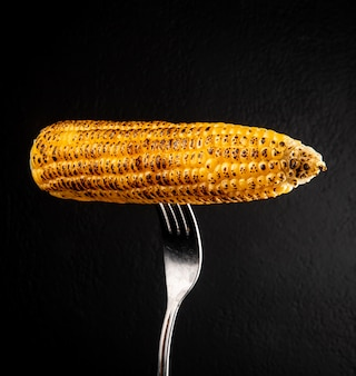 Close-up view of corn cob with fork on black wall