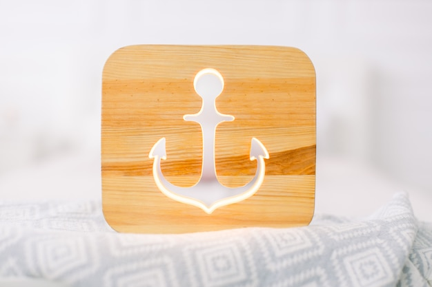 Close up view of cozy wooden night lamp with anchor cut out picture, on gray blanket at cozy light bedroom interior.
