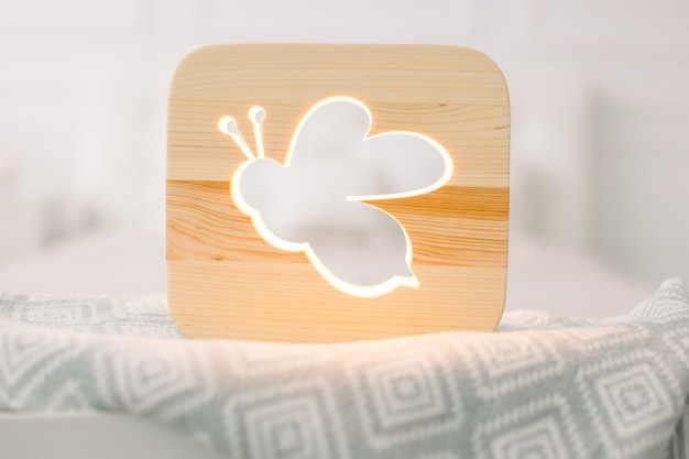 Close up view of cozy wooden night lamp with bee or insect cut out picture, on gray blanket at cozy light bedroom interior