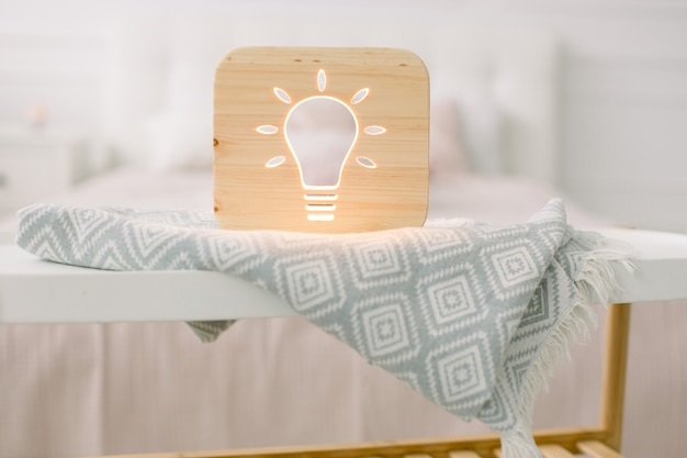 Close up view of cozy wooden night lamp with electric bulb cut out picture, on gray blanket at cozy light bedroom interior.