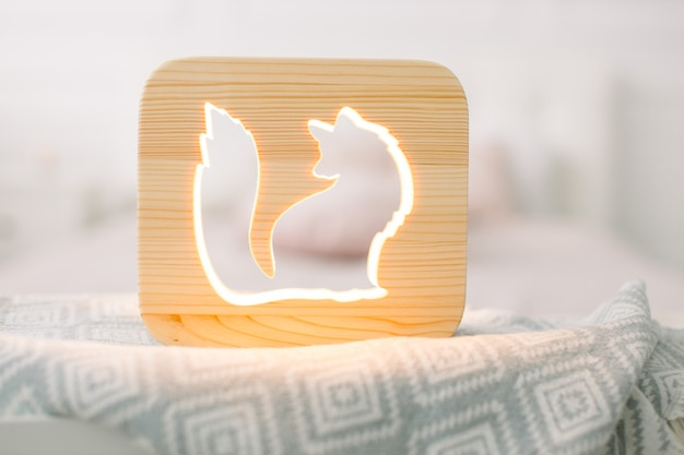 Close up view of cozy wooden night lamp with fox cut out picture, on gray blanket at cozy light bedroom interior.