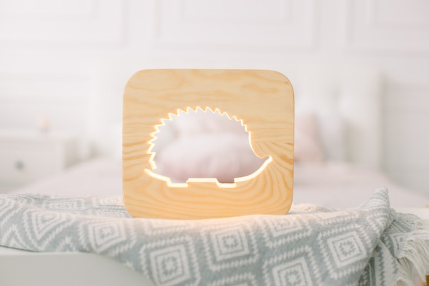 Close up view of cozy wooden night lamp with hedgehog cut out picture, on gray blanket at cozy light bedroom interior.