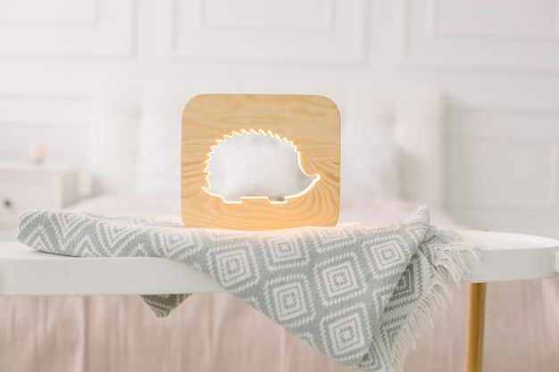 Close up view of cozy wooden night lamp with hedgehog cut out picture, on gray blanket at cozy light bedroom interior