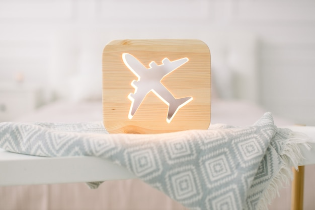 Close up view of cozy wooden night lamp with plane cut out picture, on gray blanket at cozy light bedroom interior.