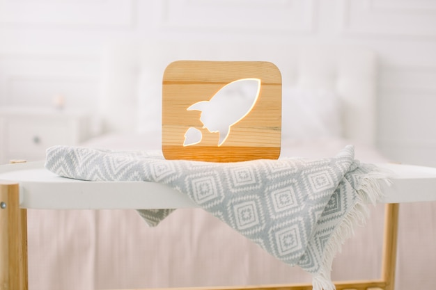 Close up view of cozy wooden night lamp with rocket cut out picture, on gray blanket at cozy light bedroom interior