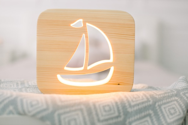 Close up view of cozy wooden night lamp with ship cut out picture, on gray blanket at cozy light bedroom interior.