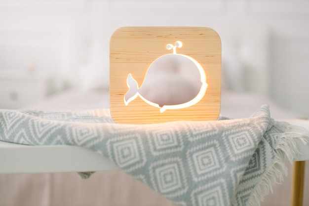 Close up view of cozy wooden night lamp with whale cut out picture, on gray blanket at cozy light bedroom interior.
