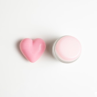 Close-up view of a cream and heart on white background