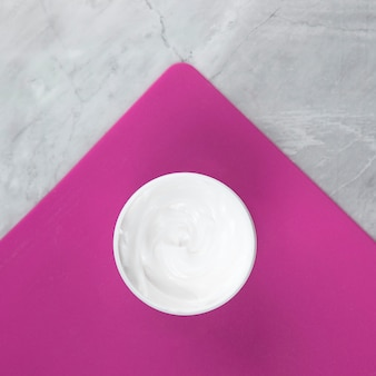 Close-up view of a cream on pink and marble background