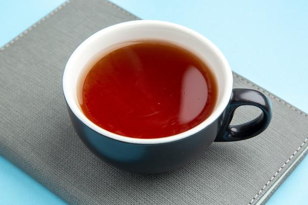 Vista ravvicinata di una tazza di tè nero su un taccuino grigio su superficie blu