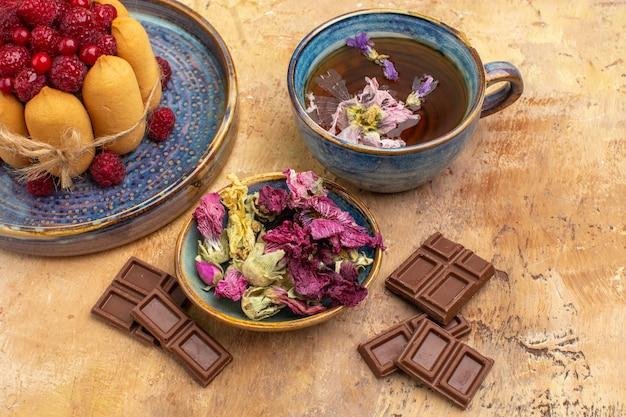 Vista ravvicinata di una tazza di tisana calda morbida torta con frutta e fiori barrette di cioccolato