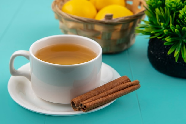 Close-up view of cup of tea and cinnamon on saucer with basket of lemons on blue background